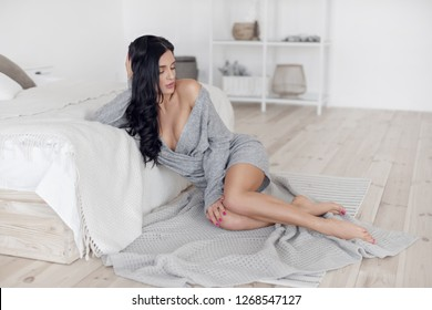 Sexy brunette with beautiful breasts sitting in the bedroom near the bed in a gray sweater