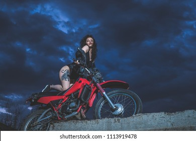 Sexy brunette biker girl sits on a motorcycle