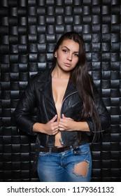 Sexy brunette in black jacket posing near the wall