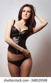 Sexy brunette in black latex corset