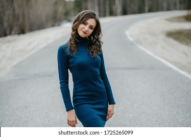 Sexy brunette in a blue dress, posing against the background of the roadway. Beautiful natural makeup. A woman with a perfect figure