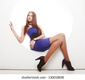 sexy brunette in blue dress sitting in a circle