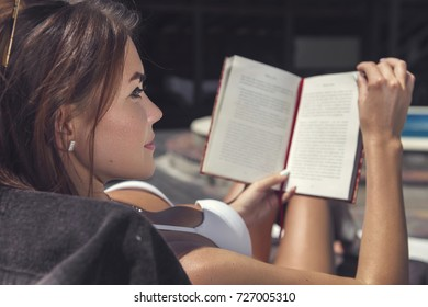 Sexy brunette caucasian woman get tan near swimming pool in a white bikini. She young and fit with healthy skin. Girl reading a book, focus on it