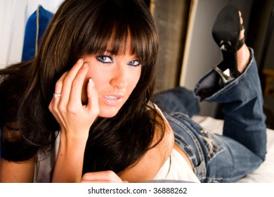 sexy brunette female fashion model in casual clothing in the studio