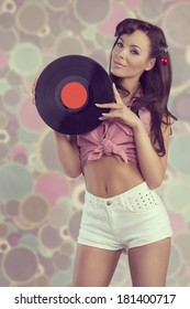 sexy brunette female pin-up with sexy shorts posing with vinyl Lp in the hands