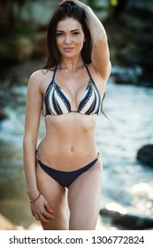Sexy brunette girl in bikini posing on a beach