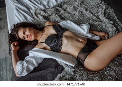 Sexy brunette girl in black lingerie is lying on the bed