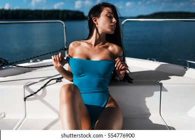 sexy brunette girl in blue swimsuit on luxury white yacht