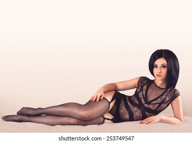 Sexy brunette girl laying in black lingerie full length on a bright background with copyspace