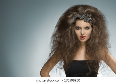 sexy brunette girl with long curly voluminous hair-style and glitter accessory in the hair posing in fashion portrait with cute make-up