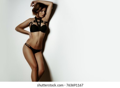 sexy brunette girl posing in black lingerie in the studio on a white background