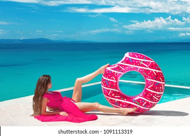 Sexy brunette Girl relaxing with inflatable float ring by the hotel infinity pool at exotic island. Travel vacation carefree woman enjoying sumer vaction. Tropical beach lifestyle.