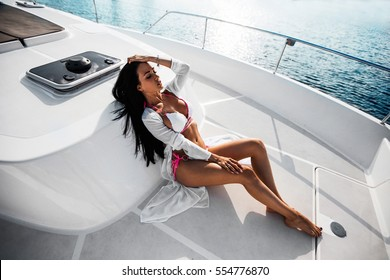sexy brunette girl in white swimsuit on luxury white yacht