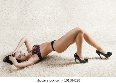 sexy brunette laying on a white carpet and wearing an elegant black lingerie, she looks in to the lens and has both hands on the head