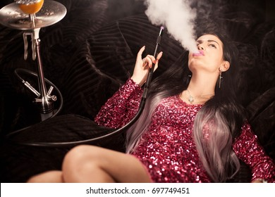Sexy brunette lying and exhaling hookah smoke near a big shisha.