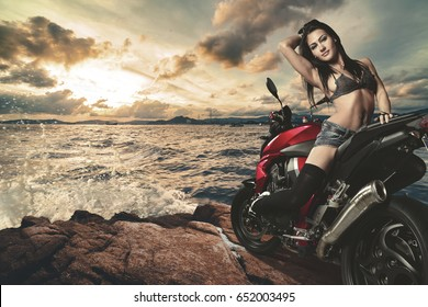 Sexy brunette on the bike on the shore