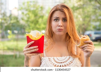 Sexy brunette plus size model eating burger and fries as her diet cheat meal. Outdoors. Copy space