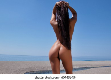 Sexy brunette posing nude on the beach