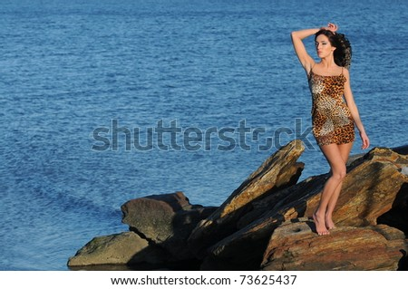 48befa1a50 Sexy Brunette posing on the beach rocks in Victoria s Secret swimsuit and  leopard mini dress