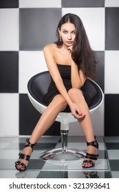 Sexy brunette posing on a chair in the studio