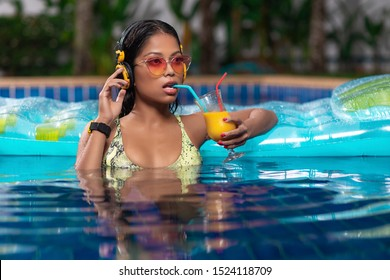 Sexy brunette posing in the pool near a mattress, drinking a cocktail from a straw, in yellow headphones and a wristwatch with yellow-pink gradient sunglasses, a green bikini.