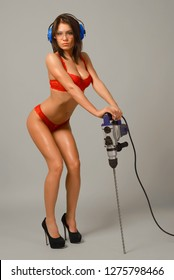 sexy brunette in red lingerie goggles and headphones crouching with his hands on the puncher isolated on gray background