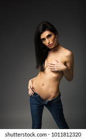 Sexy brunette topless in blue jeans on a gray background