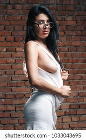 Sexy brunette topless girl on background of peeling wall with beautiful breast passionate portrait of woman, female in glasses