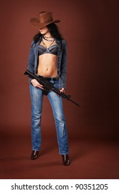 Sexy brunette wearing a cowboy hat with a rifle