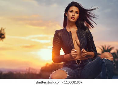 Sexy brunette wearing leather jacket and jeans posing at sunset