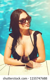 Sexy brunette woman with big tits in swimsuit posing in swimming pool at hot summer. Beautiful sexy hot girl with perfect body and big boobs posing in fashionable black swimsuit, relaxing on blue pool