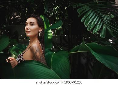 Sexy brunette woman in bikini walking in jungles with tropical palm trees, wearing beach bikini and looking at camera. Female model posing on tropic paradise resort.