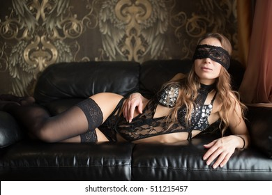 Sexy brunette woman in black lingerie lying on a sofa with blindfold