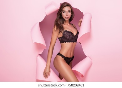 Sexy brunette woman going out from pink torn background, wearing lingerie. Girl looking at camera.