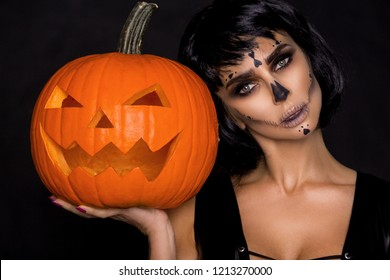 Sexy brunette woman in Halloween makeup and lingerie hold a pumpkin on a black background in the studio. Make-up skeleton, monster and witch