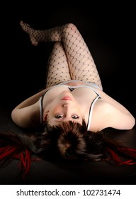 Sexy brunette woman in lingerie and fishnet stockings lying on her back looking seductively back at the camera
