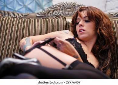 Sexy brunette woman lying on sofa in black lingerie
