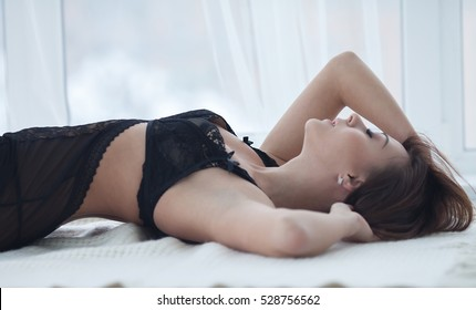 Sexy brunette woman with perfect beautiful shape of body in black erotic lingerie lying on bed