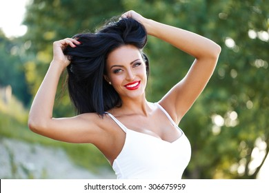 Sexy brunette woman playing with hair outdoor
