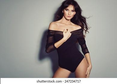 Sexy brunette woman posing in black bodysuit