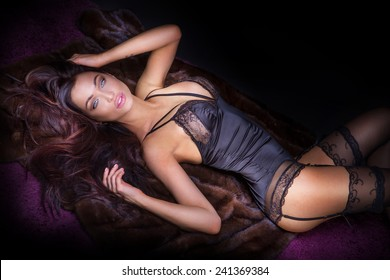 Sexy brunette woman posing in elegant lingerie, looking at camera. Girl with perfect body lying, relaxing.