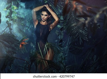 Sexy brunette woman posing in fashionable lingerie in jungle
