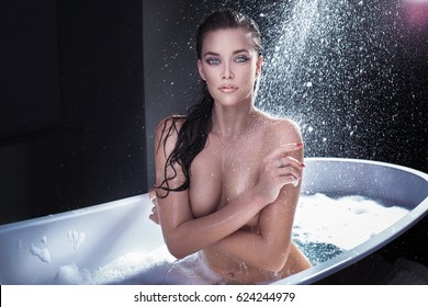 Sexy brunette woman posing naked with wet hair, bathing.