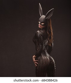sexy brunette woman posing in rabbit black mask and bodysuit back shot