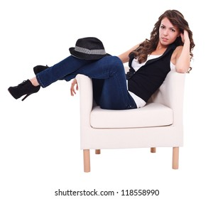 Sexy brunette woman sitting in armchair, posing to camera
