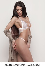 Sexy brunette woman in underwear posing, isolated on grey, sensuality