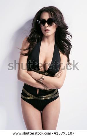 214843b30f Sexy brunette woman wearing black swimwear with sunglasses posing on white  background. Perfect body