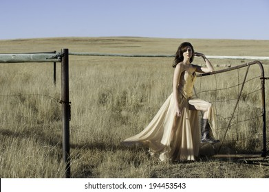 Sexy brunette woman wearing a gold evening dress with gum boots, posing outside in a field in the sun against a rusty metal farm gate.