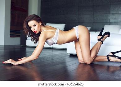 Sexy brunette woman in white underwear kneeling on floor, red lips, glamour