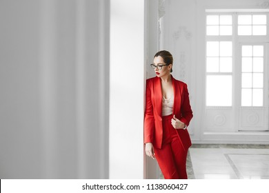 Sexy business lady, plus size model girl in stylish glasses and in red fashionable suit posing near the window at white interior